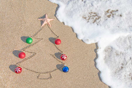 beach happy new year: Christmas tree contour with decorations, star and wave on the beach - holiday vacation concept