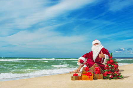 Santa Claus at sea beach with many gifts and decorated christmas tree - happy new year concept Banco de Imagens
