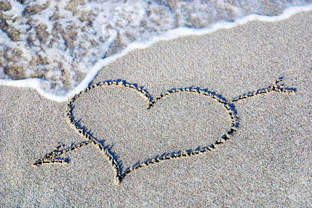 heart in sand: heart outline with arrow on the wet brilliance beach sand against wave