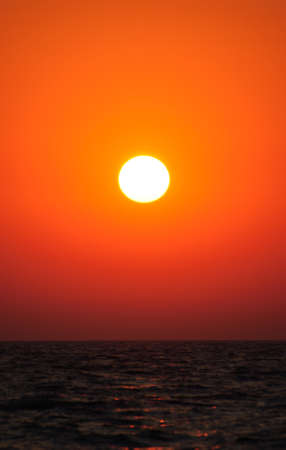 rise and shine: Bright vertical sunset under the sea surface