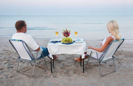 A young couple share a romantic dinner with candles and wine glasses on the sea sand beach photo