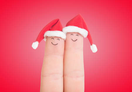 christmas day: Fingers faces in Santa hats isolated on white background. Happy couple celebrating concept for Christmas day. Stock Photo