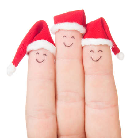 christmas day: Fingers faces in Santa hats isolated on white background. Happy family celebrating concept for Christmas day. Stock Photo