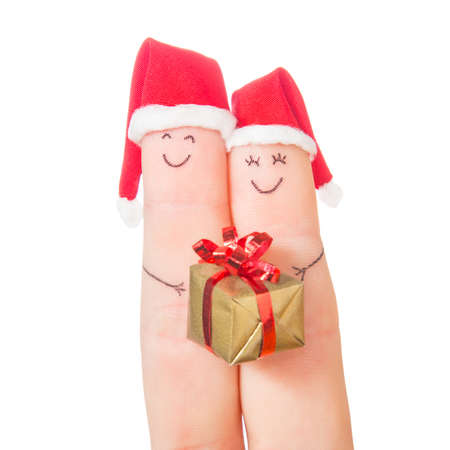 Fingers faces in Santa hats  with gift box isolated on white background. Happy couple celebrating concept for Christmas day. photo