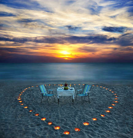 romantic dinner on sea beach with candle heart in Maldives Stock Photo