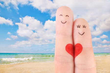 family vacation concept - a man and a woman hold on the red heart, painted at fingers against beautiful sea sand beach