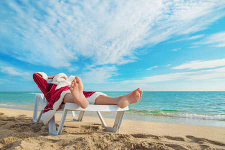 beach feet: sunbathing Santa Claus relaxing in bedstone on tropical sandy beach - Christmas concept