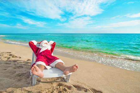 Zonnebaden Kerstman ontspannen in bedstone op tropische strand - concept van Kerstmis Stockfoto - 34762959