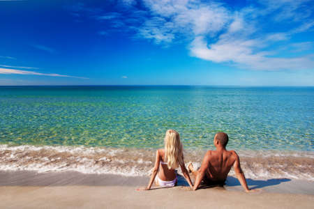 young couple sitting on the sea sand beach and looking at sky photo