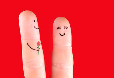 relationship love: happy couple concept - a man with flower and a woman,painted at fingers isolated on red background