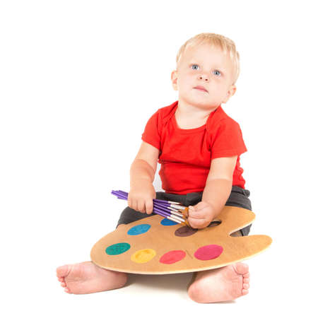 year-old child as small artist with paint brushes and color palette photo