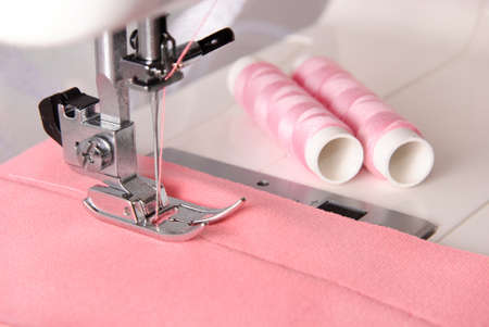 seamstress: sewing process of rosy cloth on the machine and two bobbins background