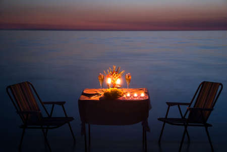 romantic dinner on the sea beach with candles and wine