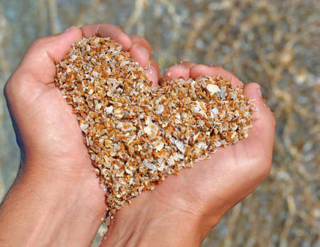 심장의 형태로 모래를 손에 들고