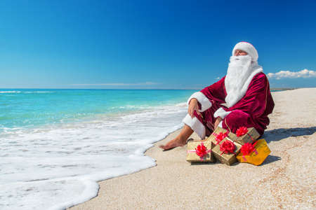 Santa Claus with many golden gifts relaxing on sea beach  - christmas  or happy new year concept 스톡 콘텐츠