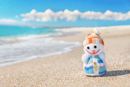Smiley toy snowman at sea beach. Holiday concept for New Years and Christmas Cards.