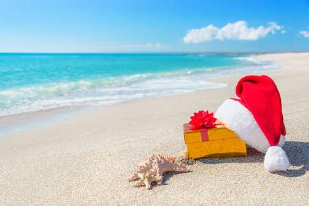 Čepice Santa Claus a zlaté vánoční dárkové krabici na pobřeží s výhledem na moře hvězdami proti modré obloze