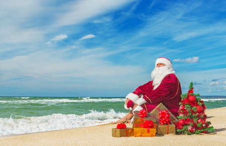 Santa Claus at sea beach with many gifts and decorated christmas tree - happy new year concept 스톡 콘텐츠