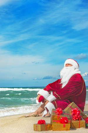 산타 클로스 바다 해변에서 휴식 많은 황금 선물 - 크리스마스 또는 새 해 복의 개념