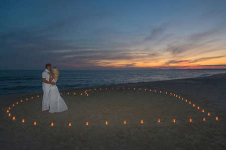 Young couple in candles heart at sea beach against sunset- St.Valentines Day romantic concept