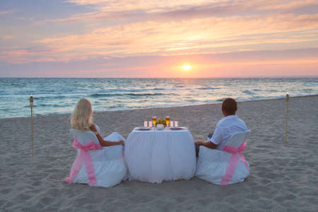 Couple at sea beach during luxury romantic dinner, with candles and torches flame against beautiful sunset photo