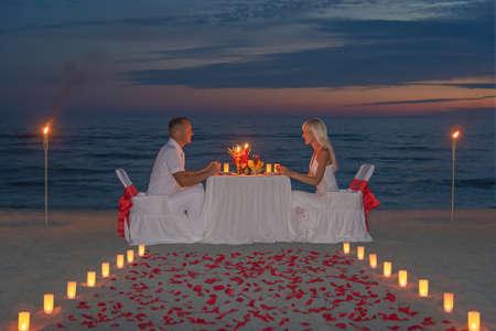 몇 촛불, 횃불과 방법 또는 장미 꽃잎 일몰과 함께 바다 모래 해변에서 낭만적 인 저녁 식사를 공유 스톡 콘텐츠