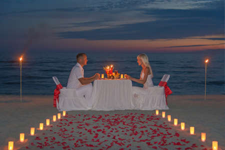 couple share a romantic dinner with candles, torches and way or rose petals at sea sandy beach against sunset Reklamní fotografie