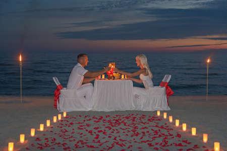 paar delen een romantisch diner met kaarsen, fakkels en manier of rozenblaadjes op zee zand strand tegen zonsondergang Stockfoto