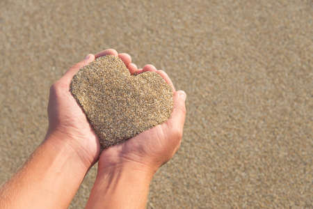 Hands holding a sand in form of the heart