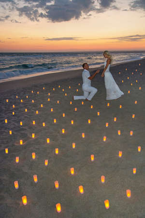 enamoured couple at sea beach in candles against bright sunset - St.Valentines Day romantic concept