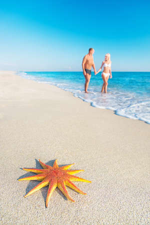 Lovers couple at sandy sea beach with  big red starfish - hot countries holidays concept photo