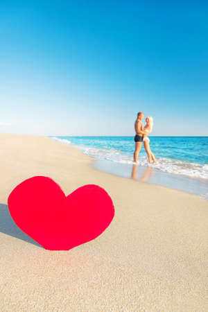 st valentine's day: Lovers embrace couple at sea beach and big red heart - St. Valentines Day concept Stock Photo