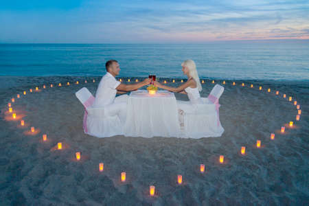 Young couple during romantic dinner with heart of candlelights on tropical sandy sea beach