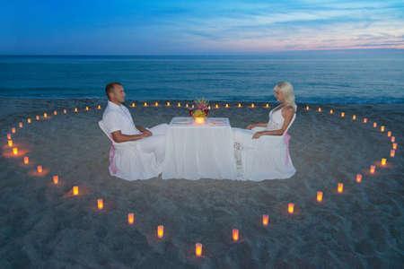 열대 모래 바다 해변에서 촛불의 마음으로 낭만적 인 저녁 식사 동안 젊은 부부 스톡 콘텐츠
