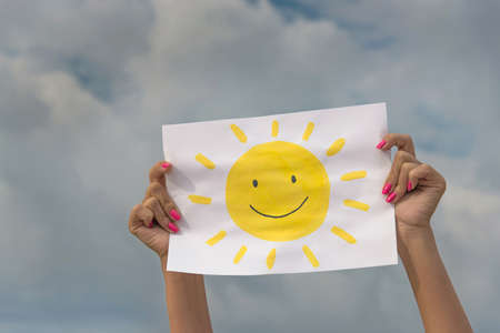 human hands with sheet of paper with sun image against overcast sky - positive thinking concept