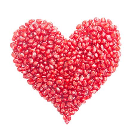 heart-shaped pomegranate seeds isolated on white background