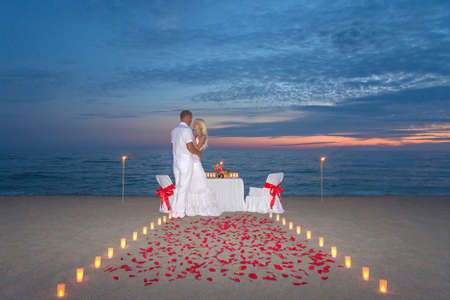 Young couple share a romantic dinner with candles, torches and way or rose petals at sea sandy beach against sunset