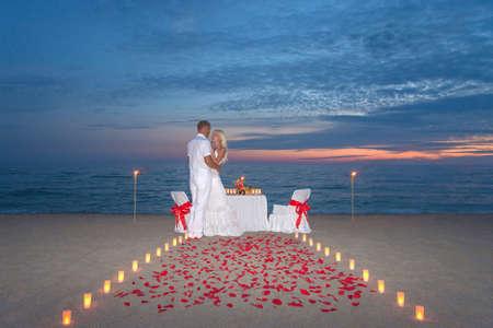 diner romantique: Jeune couple part un d�ner romantique avec des bougies, torches et mani�re ou p�tales de rose sur la plage de sable de mer contre le coucher du soleil Banque d'images