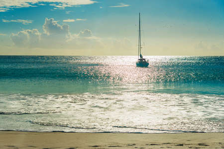 Yacht at tropical sandy beach at sunset. Anse Georgette, Praslin island, Seychelles - vacation background
