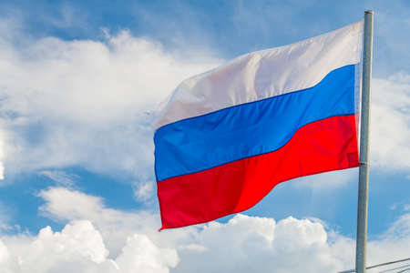 Russian flag waving in the wind over blue sky with white clouds