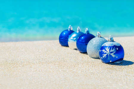 Christmas tree decorations on sea beach sand - winter holidays in hot countries concept photo