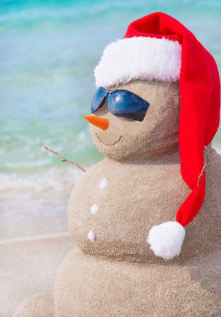 beach happy new year: Sandy christmas snowman in red santa hat and sunglasses at sunny beach. Holiday concept for New Years Cards. Stock Photo