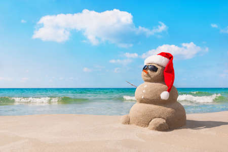 beach summer: Sandy christmas snowman in red santa hat and sunglasses at sunny beach. Holiday concept for New Years Cards. Stock Photo