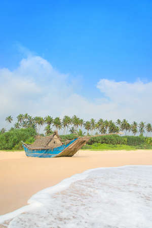 skiff: Fishing boat at beautiful sandy ocean palm beach, Indian Ocean Stock Photo