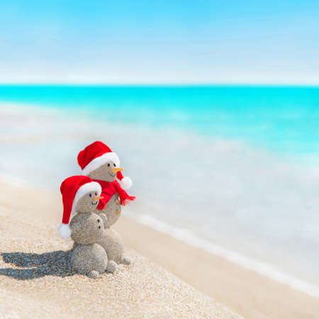 Smiley sandy snowmen couple at sea beach in christmas hat. New years holiday in hot countries concept. Standard-Bild