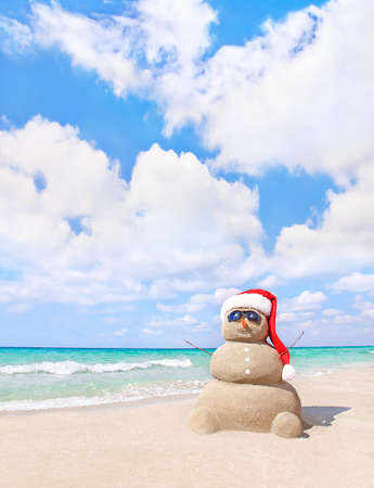 Smiling sandy snowman in red santa hat on sea beach. New Years and Christmas holidays in hot countries concept.