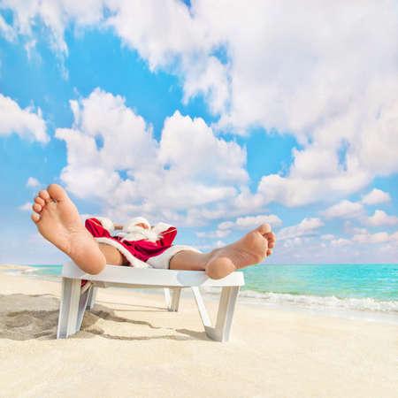 크리스마스 또는 새해 개념 - 산타 클로스 바다 해변에 긴 의자에서 휴식을