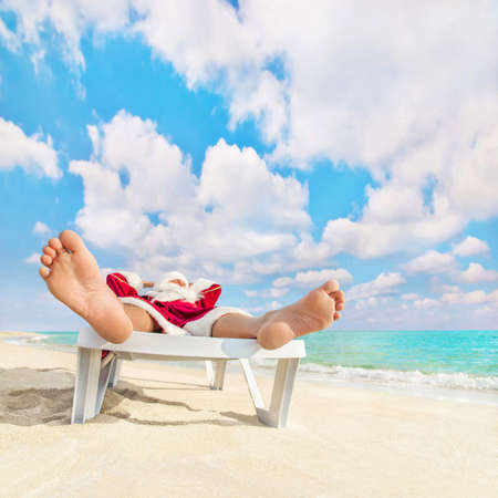 Santa Claus have a rest in chaise longue on sea beach - christmas or happy new year concept Stock Photo