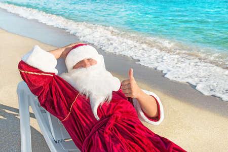 산타 클로스 바다 해변에 긴 의자에 전자 휴식을 - 크리스마스 또는 새해 개념을