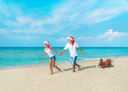 Happy young couple running at sea beach in red santa hats with gifts, sled and decorated christmas tree - holiday concept photo